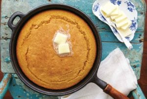 A cast iron skillet filled with cooked sweet potato cornbread topped with two pats of butter, resting on a old blue wooden chair with a dish of butter beside it.