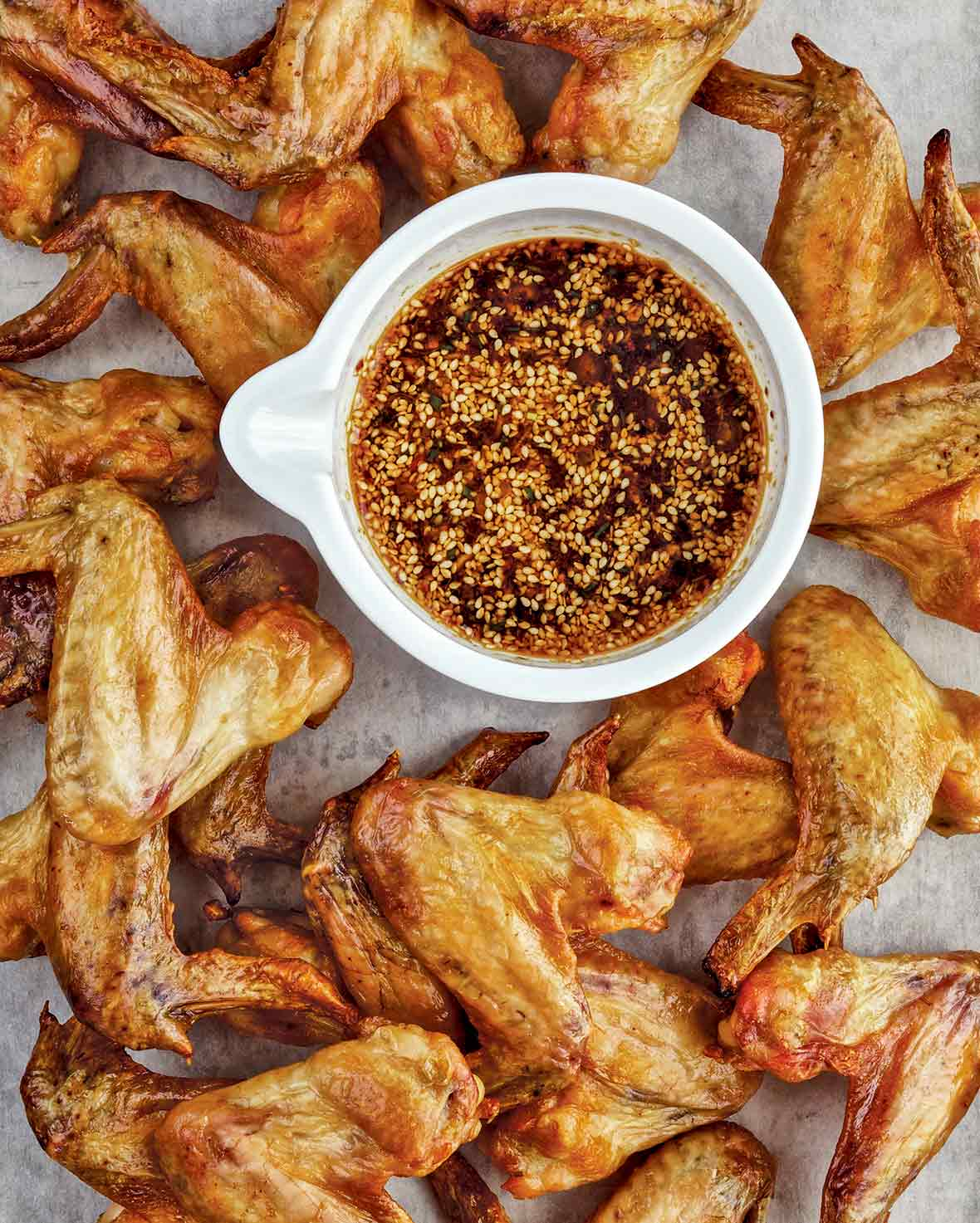 A pile of roasted chicken wings with a bowl of Korean dipping sauce with sesame seeds