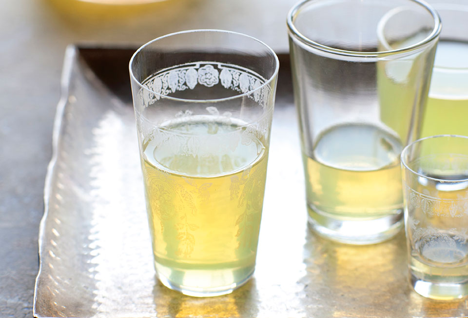 Several glasses partially filled with limoncello on a silver platter, with a bottle of limoncello in the background.
