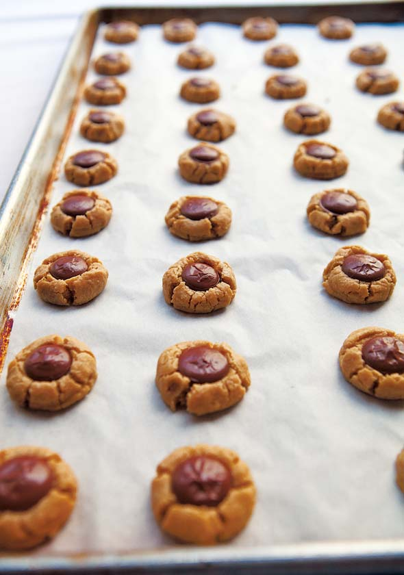 A parchment lined baking sheet filled with rows of round peanut butter cookies with chocolate centers.