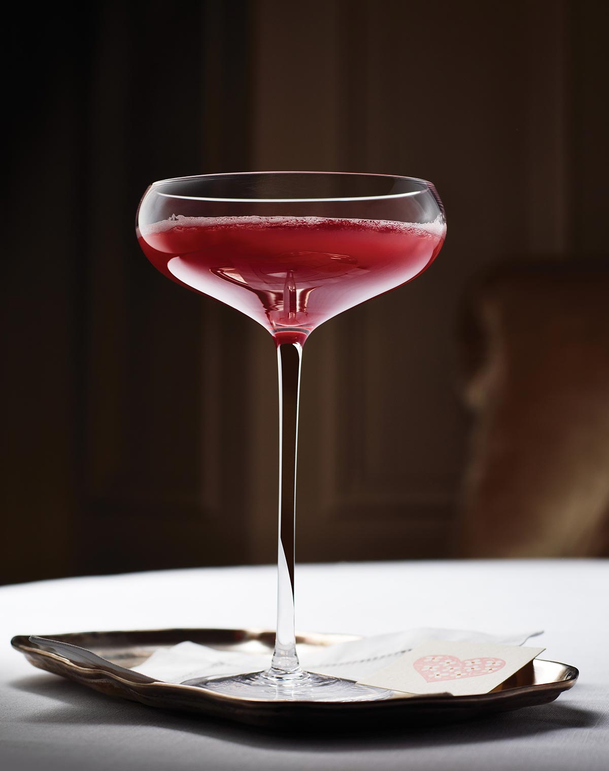 A coupe glass filled with blood orange prosecco cocktail on a small tray.