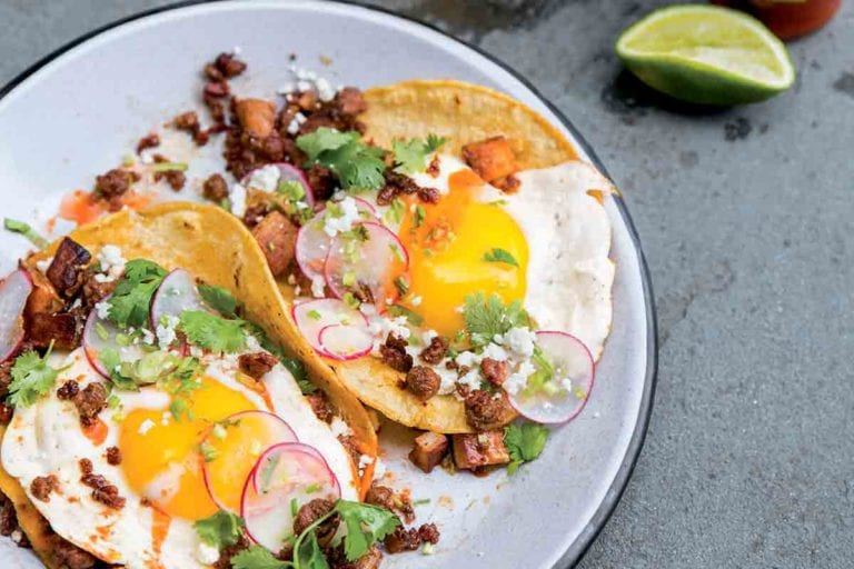Two chorizo breakfast tacos with potatoes, eggs, radish, chorizo, cilantro, and Cotija cheese on a white plate.