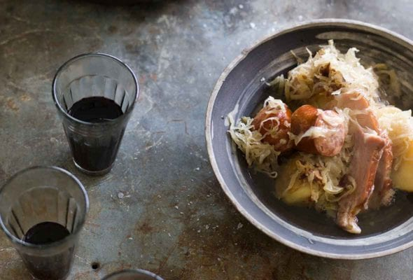 A Dutch oven and a porcelain bowl filled with choucroute garnie, made with pork, sausage, and sauerkraut, with two glasses of wine on the side.