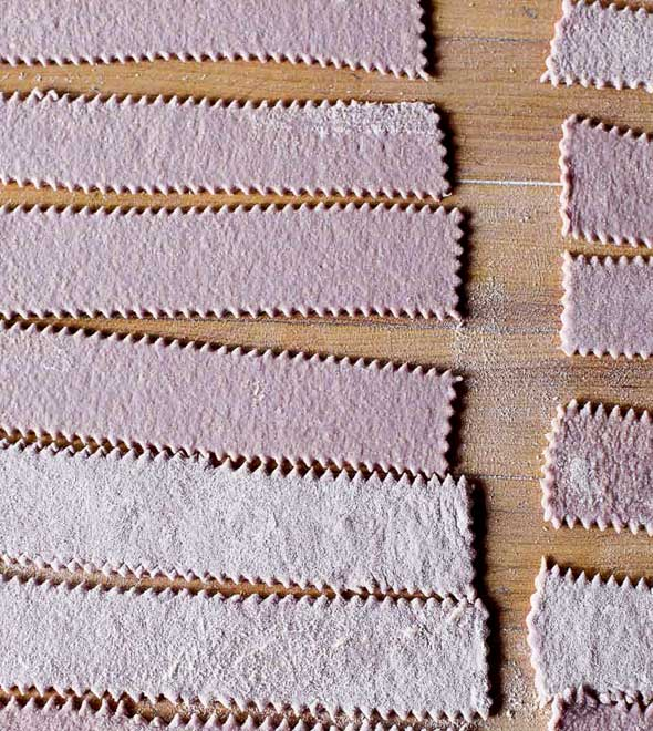 Long strips of fresh homemade red wine pasta laid on a wooden board