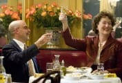 Julie and Julia toasting with wine glasses raised above a table in a restaurant.