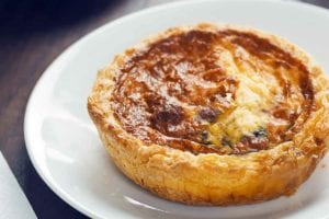 A baked mini quiche for one on a white plate.