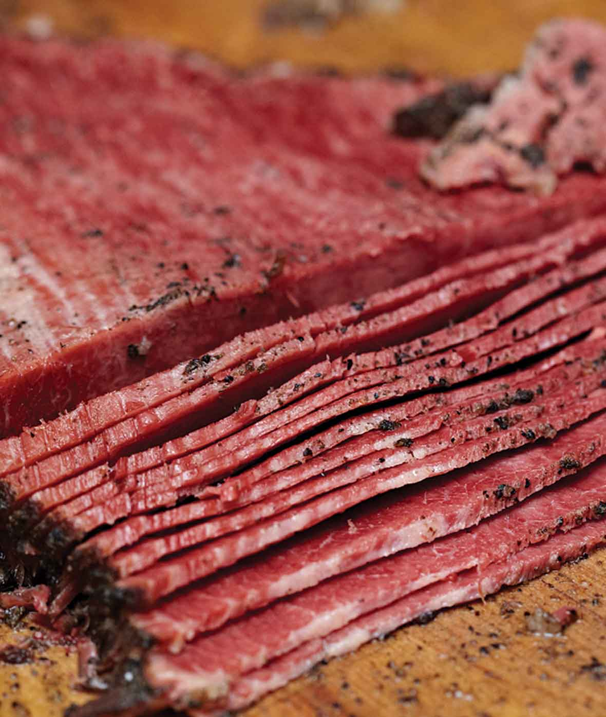 A partially sliced homemade pastrami on a wooden board.