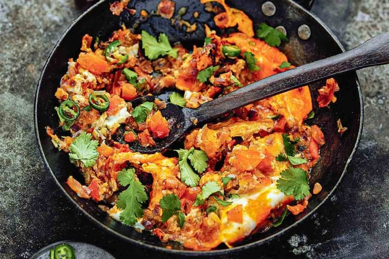 A skillet filled with spicy scrambled eggs with a wooden spoon inside.