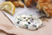 A dollop of homemade tartar sauce on a piece of newspaper with fried fish and a lemon wedge beside it.
