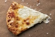 A slice of white pizza on a brown background with flaked salt scattered over and around it.