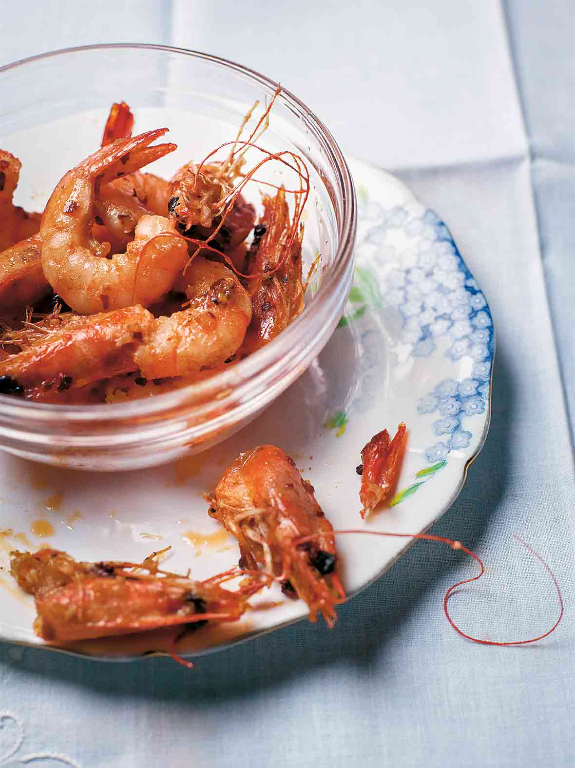 Glass bowl filled with garlic shrimp, sautéed with oil, butter, chiles pepper, and garlic