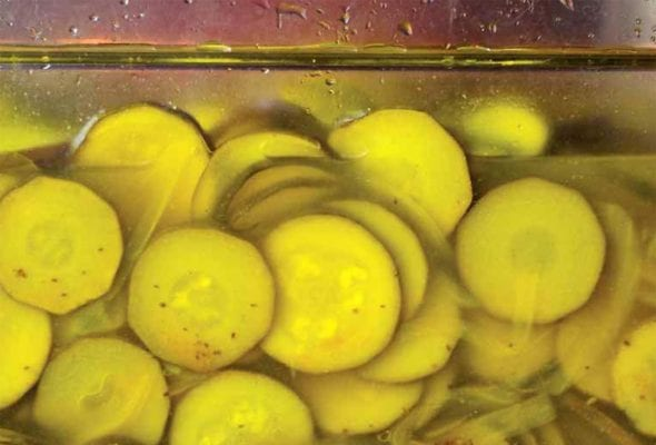A close up view of a full jar of pickled zucchini.