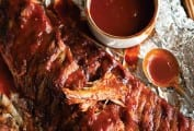 Two slabs of BBQ ribs on a piece of foil with a dish of sauce and a spoon nearby.