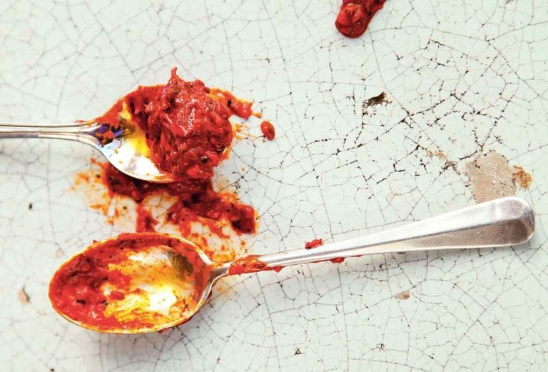 Two spoons with homemade harissa on them on a cracked enamel surface.