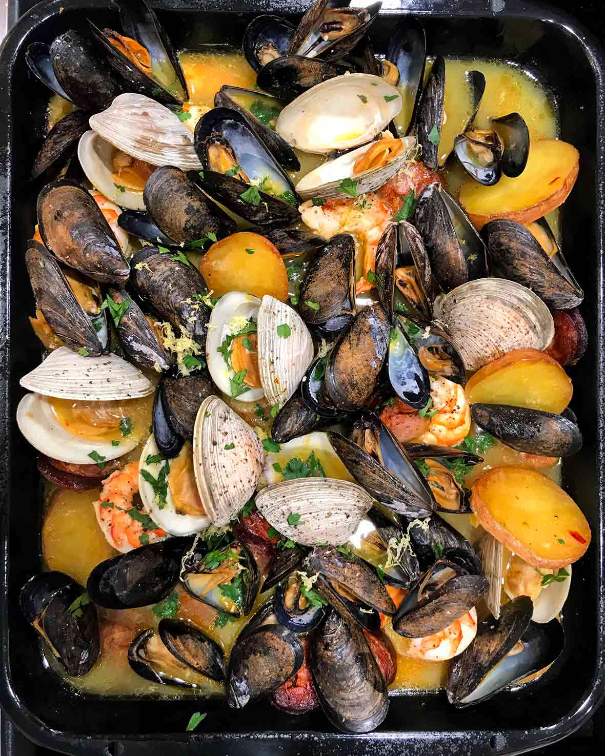 Pan of seafood and chorizo stew with clams, mussels, shrimp, and potatoes in a saffron broth