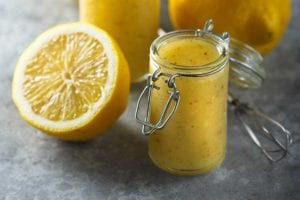 Two jars of lemon vinaigrette, two lemon halves, and a wire whisk.
