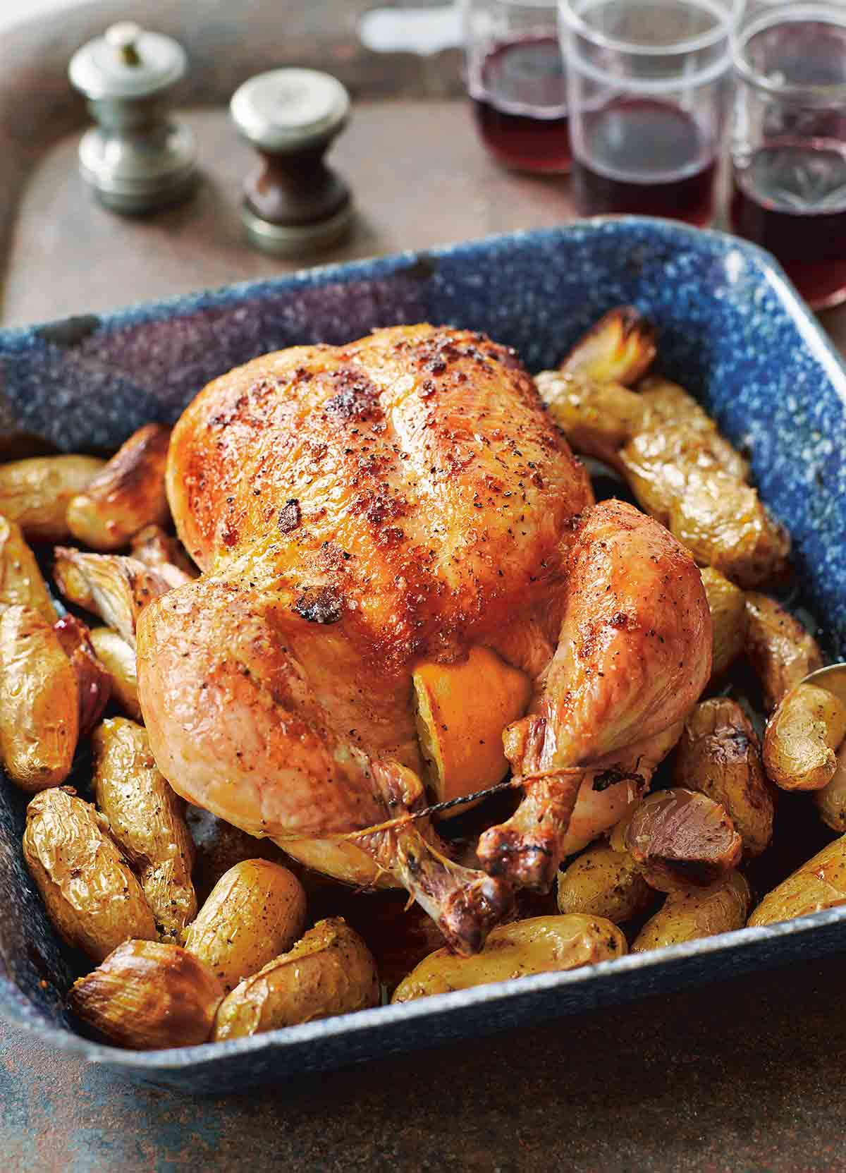 A whole maple roast chicken set on top of potatoes and shallots in a blue baking dish.