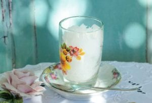 A glass filled with ouzo sorbet in a small china dish with a spoon resting beside it.