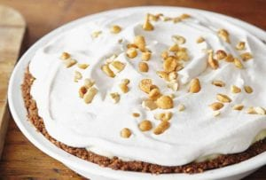 A whole peanut butter pie, topped with crushed peanuts on a wooden table.