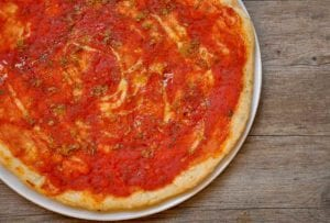 A tomato pizza, called pizza marinara, on a plate with oregano and garlic