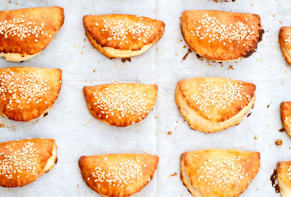 Twelve Turkish borekitas sprinkled with sesame seeds on a piece of parchment.