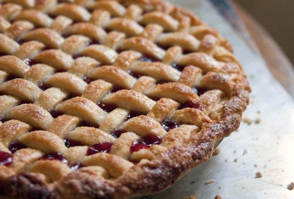 A lattice-topped cherry pie on a baking sheet.
