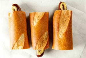 Three servings of hot dog on a baguette with mustard on a paper napkin.