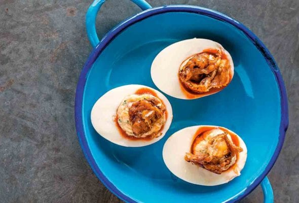 A blue pot containing three deviled eggs with roast chicken skin.
