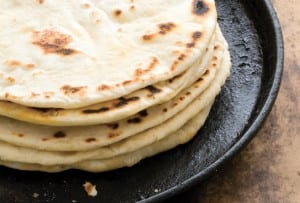 A stack of flour tortillas with bacon fat on a cast-iron skillet.