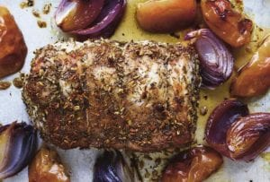 A roast pork loin with apples and onions scattered around it on a baking sheet.