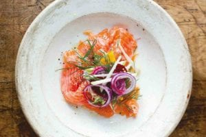 A white plate with salmon, fennel, and apple salad topped with red onion and dill.