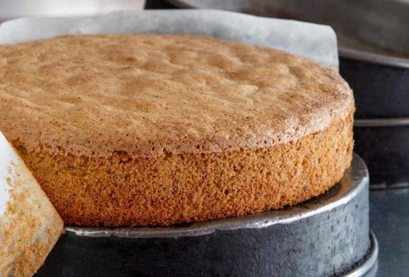 A spiced nut cake resting on an upside-down cake pan with a strip of parchment half removed from the edges of the cake.