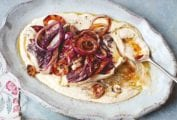 An oval platter filled with white bean puree, radicchio, and red onions with a spoon resting in it and a serving in a bowl beside.