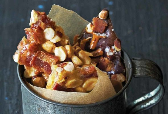Tin cup lined with brown paper and filled with peanut brittle studded with bacon on blue wood