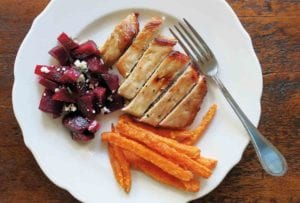 White plate with a maple pork chops, carrots, and beets with feta cheese