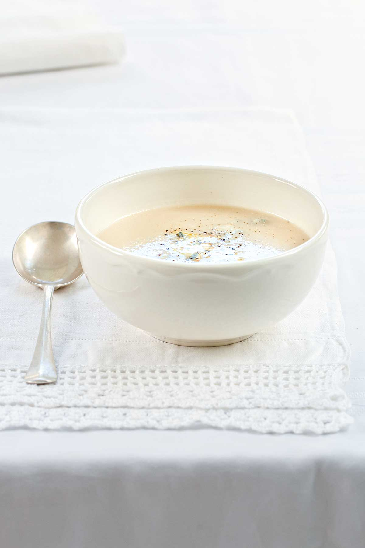 A white bowl of cauliflower soup on a white linen cloth with a spoon resting beside it.