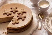 A gingerbread cheesecake with one slice missing on a decorative plate with spoons and espresso cups on the side