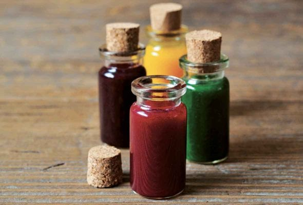 Four vials of natural food coloring--red, purple, yellow, and green