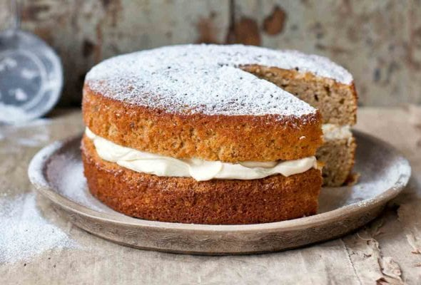 A maple parsnip cake with mascarpone frosting between the layers on a grey plate.