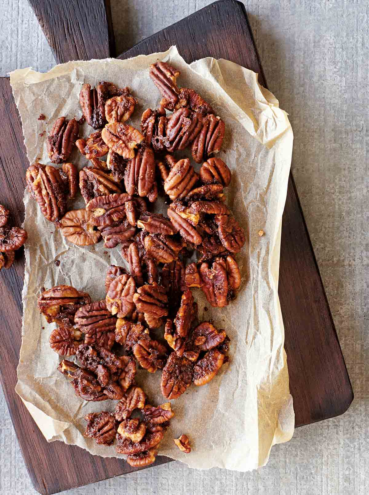 Baked spiced pecans on a sheet of parchment that is resting on a wooden serving board.