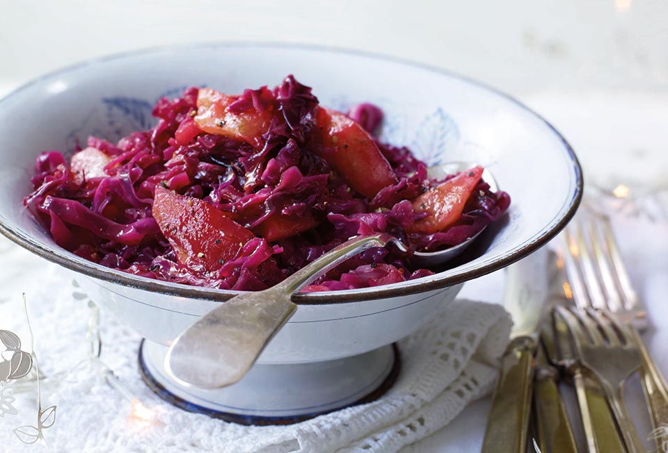 A white bowl filled with spiced red cabbage set on white linens with a spoon resting inside.