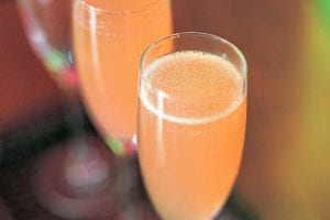 Two Champagne flutes filled with Campari fizz.