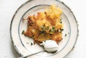 A cheddar and potato latke topped with chives and applesauce on a plate with a spoonful of sour cream beside the latke.