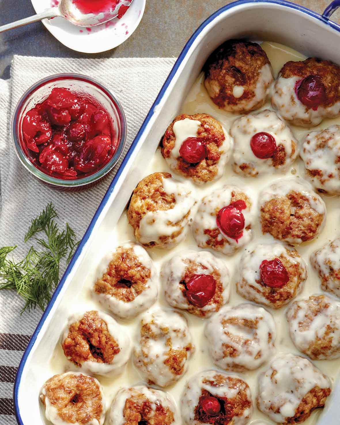 A white tray filled with Swedish meatballs--a combination of veal, pork, and beef--filled with cranberry sauce and topped with a white cream sauce