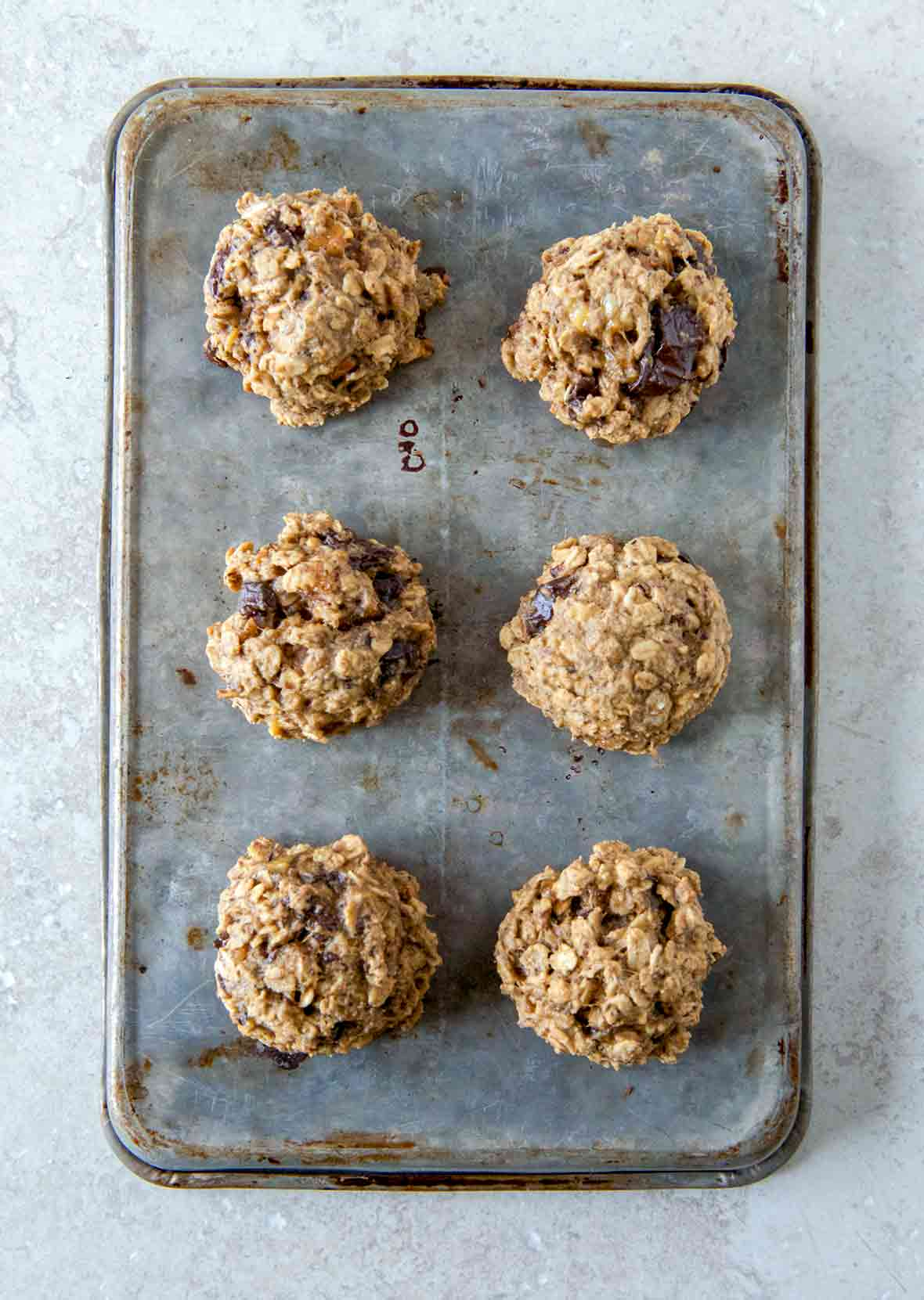 A cookie sheet with six breakfast cookies with oats, banana, figs, and peanut butter