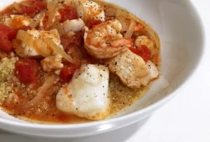 A white bowl filled with cod and shrimp stew with quinoa.