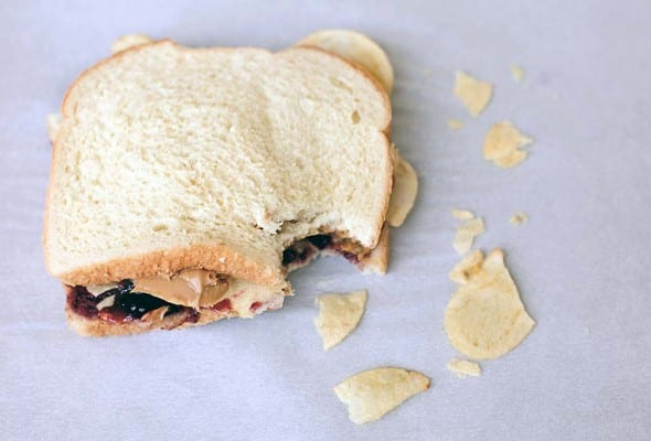 A peanut butter and jelly sandwich with potato chips with one bite gone and some chips scattered around it.