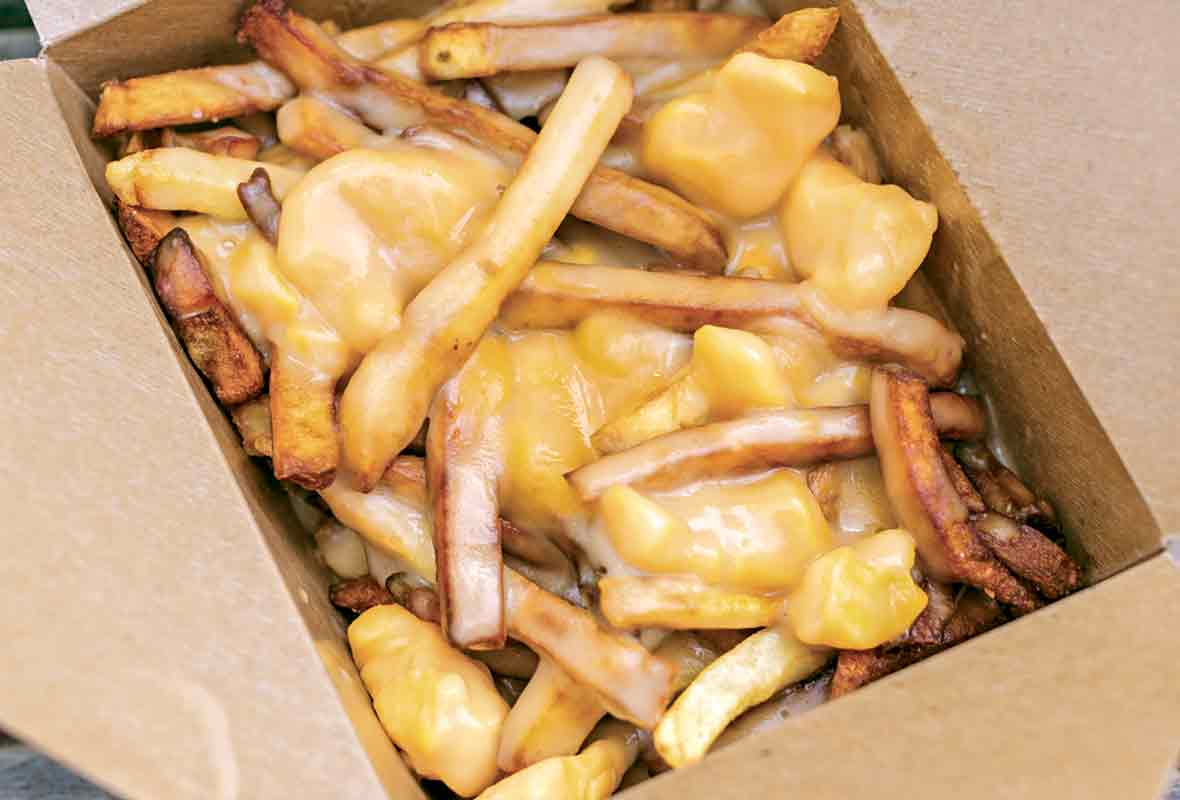 Cardboard container filled with french fries covered in melted cheese curds