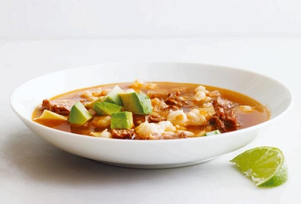 A white bowl filled with quick posole topped with avocado with a lime wedge on the side.