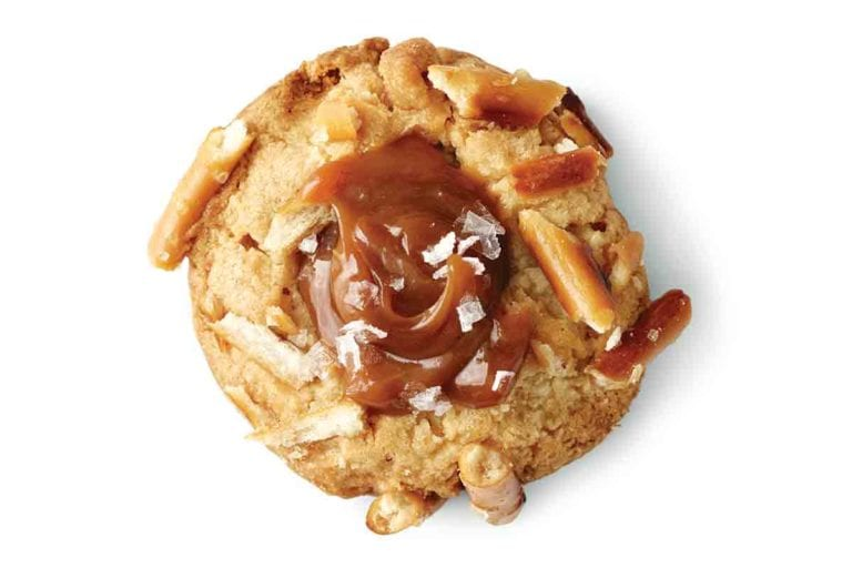 A salted caramel and pretzel cookie topped with flaked sea salt and pieces of pretzel.